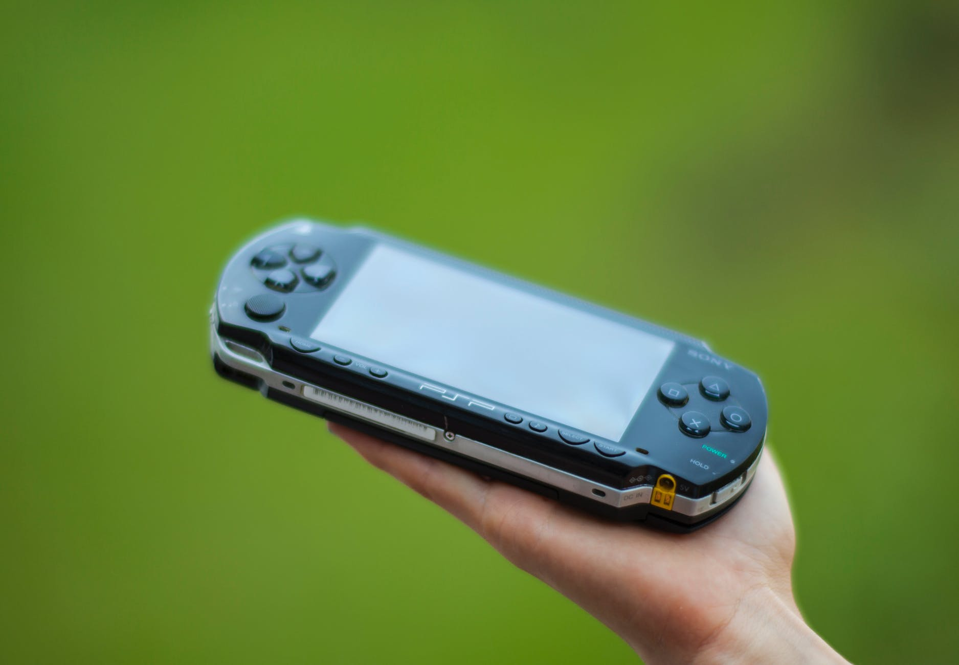 closeup photography of person holding black sony psp handheld console
